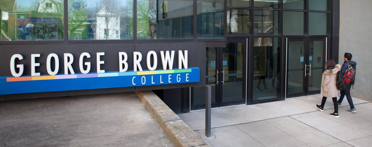 A male and female student walking towards a Casa Loma campus entrance near a George Brown College sign.
