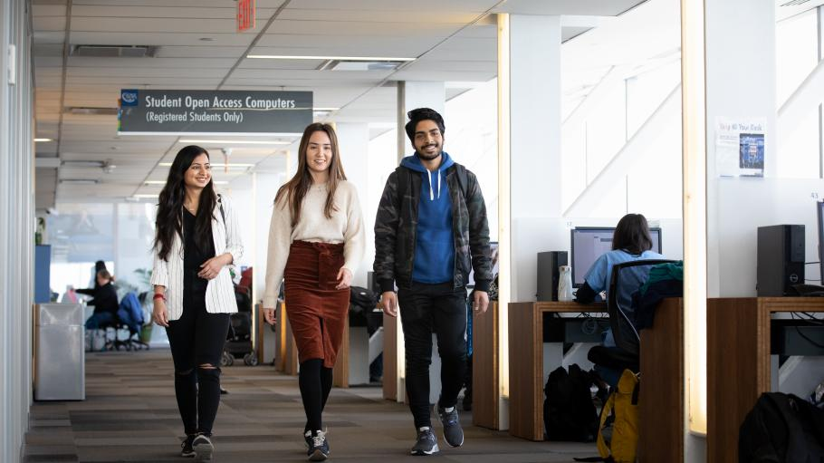 3 students walking through Waterfront Campus library