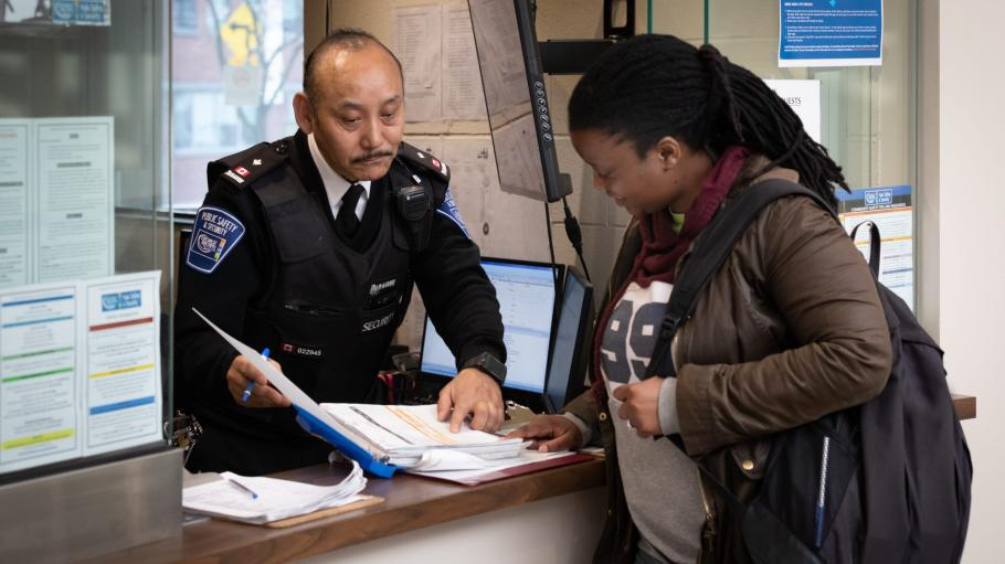 Female student talking to a male security guard at the Security desk at Casa Loma.