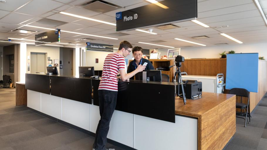 A male student showing his phone to a male staff member at the Photo ID desk at the Waterfront LLC.