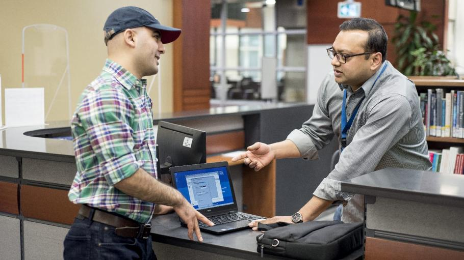 A male student is standing at the library desk and showing settings on his laptop to the librarian while the librarian is pointing at the laptop and explaining something to him.