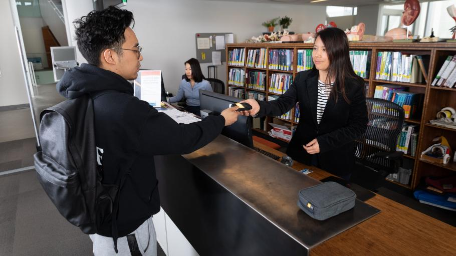 Female library staff handing a male student wifi equipment at the check-out desk.