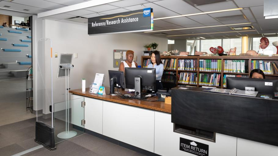 A student receiving help from one of the librarians at the Reference/Research Assistance Desk at the Waterfront Campus Library (LLC).