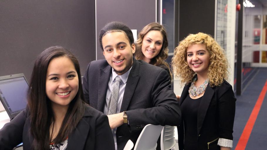 Business students sitting and posing together for a picture in business attire.