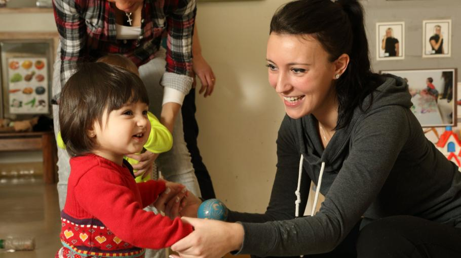 A female child care worker is squatting beside a standing girl toddler. They are both smiling.