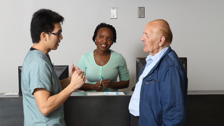 A female receptionist and a male Health Sciences student are helping an elderly visitor into the office at the receptionist desk. The elderly visitor is facing the student and having a conversation with him while the receptionist listens along.