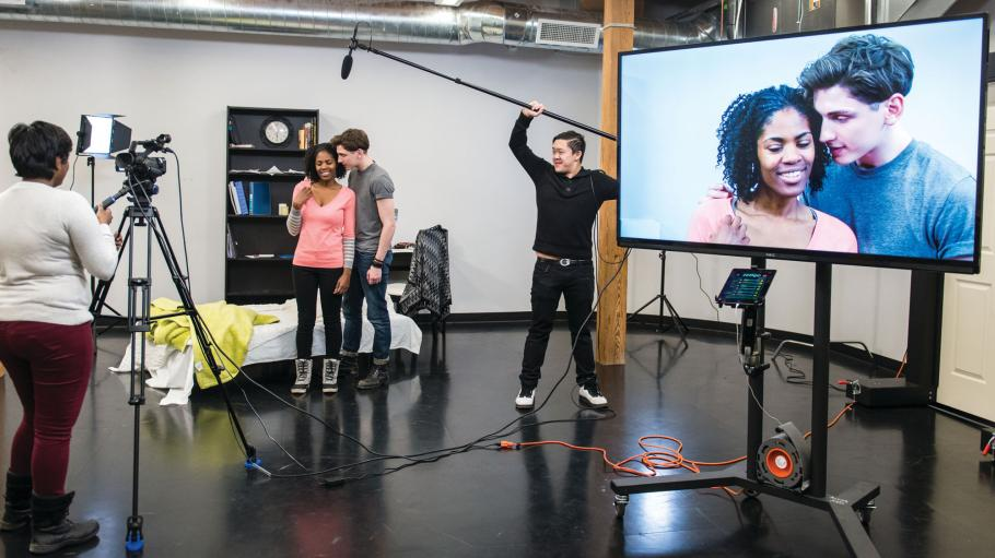 Female and male acting student are in front of the camera in a video studio and being recorded while acting. Closeup of their faces is visible on large TV screen.