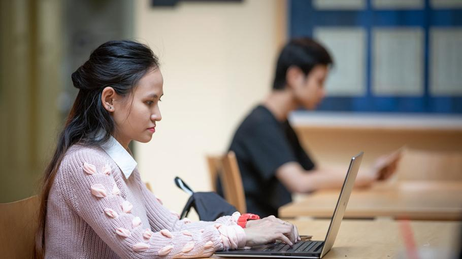 Female student using a laptop with another student in background