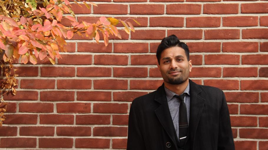 Male student posing outside of the St James patio; a brick wall is the background.