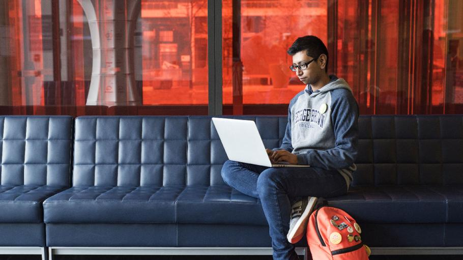 Student using laptop on couch