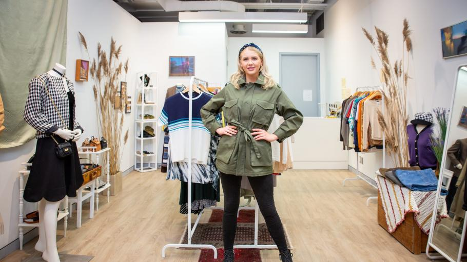 Fashion student standing in front of racks of clothing in the student-run fashion store.