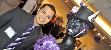 A fashion management student poses with a mannequin decoration at Fashion Works 2011.