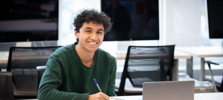 student with notepad and laptop
