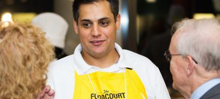 A person wearing a yellow apron facing two people with their backs to the camera at the Food Court Social.