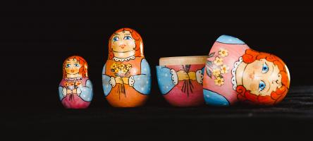 Set of three Russian dolls with the largest one open and the lid laying on its side.